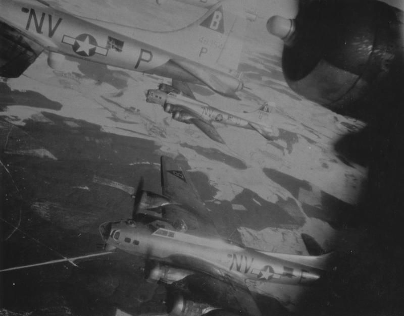 B-17 Flying Fortresses of the 92nd Bomb Group fly in formation over countryside. The aircraft, from left to right, are B-17G (NV-P, serial number 44-8354), B-17G (NV-U, serial number 42-97288) nicknamed