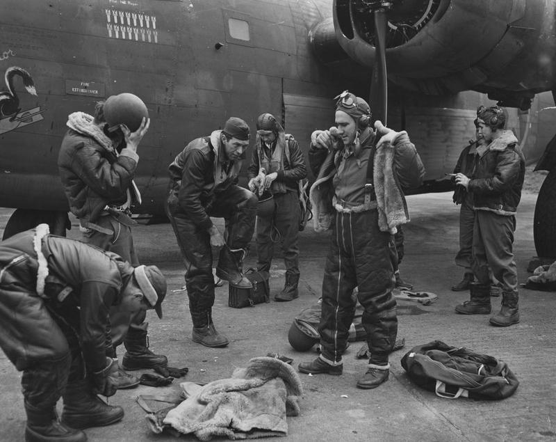 A bomber crew of the 93rd Bomb Group don their flight gear before a mission, flying a B-24 Liberator (41-23717) nicknamed