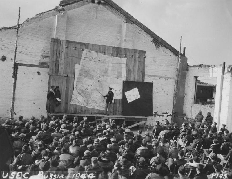 Personnel of the 96th Bomb Group  and the 452nd Bomb Group receive briefing against the wall of a bombed-out railway building in Poltava, Russia during Operation Frantic in  summer 1944.   Image via M.L. Gibson. Official caption printed on image: 'USEC, Russia 1944.'
