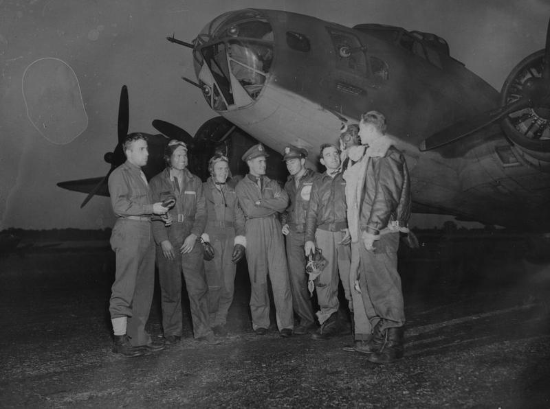 A bomber crew of the 97th Bomb Group with their B-17 Flying Fortress. They are from left to right: Lieutenant Frank R. Beadle, of Grand Rapids, Michigan; Sergeant Chester Love, of Cincinnati, Ohio; Sergeant Richard Williams, of Utica, New York; Lieutenant Levon Ray, of Poolville Texas; Glen V. Leland, of St. Petersburg, Florida; Sergeant Frank Rebello, Tiverton, Rhode Island; Sergeant Joseph Cummings, of Oskaloosa, Iowa; and Sergeant Zane Gemmill, of St. Clair, Pennsylvania. Image stamped on reverse: 'Passed for publication 18 Aug 1942' [stamp], 'Associated Press.' [stamp], 'USA(BRI)CCC' [ written annotation]. '216113'[ Censor no]. Printed caption on reverse: 'U.S. FLYING FORTRESSES RAID IN DAYLIGHT Associated press photo shows: The crew who flew the leading Flying Fortress in the raid are seen here lined up under the nose of the plane. Left to right they are Lieut. Frank R Beadle, of Grand Rapids, Michigan; Sergeant Chester Love, of Cincinnati, Ohio; Sergeant Richard Williams, of Utica, New York; Lieut. Levon Ray, of Poolville Texas; ;Glen v. Leland, of St.Petersburg, Florida; Sergeant Frank Rebello, Tiverton, Rhode Island; Sergt Joseph Cummings, of Oskaloosa, Iowa; and Serg. Zane Gemmill, of ST. Clair, Penn. AKP/ROB 249453 18842a.'