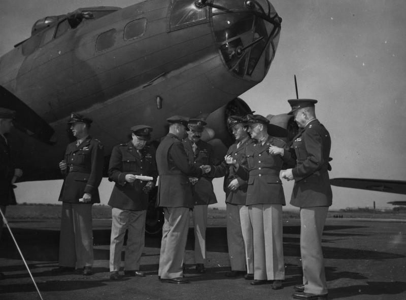 United States Air Chiefs of the European Theatre of Operations stand with a B-17 Flying Fortress of the 97th Bomb Group. Left to right these are: Major-General Frank, Brigadier-General Ira Eaker, Brigadier-General Robert Candee, Brigadier-General Frank O'Driscoll Hunter, Major-General Karl Spaatz and Lieutenant-General Dwight D. Eisenhower. Image stamped on reverse: 'Associated Press.' [stamp], 'Passed for Publication 2 Aug 1942.' [stamp] 'USA (BRI) CCC: STF.' [written annotation] and '213540.' [Censor no.] A printed caption was previously attached to the image, the caption from the next image in the sequence reads: 'U.S AIR CHIEFS IN BRITAIN. Associated Press Photo Shows: Standing before Flying Fortress, symbol of U.S. Air Power.'