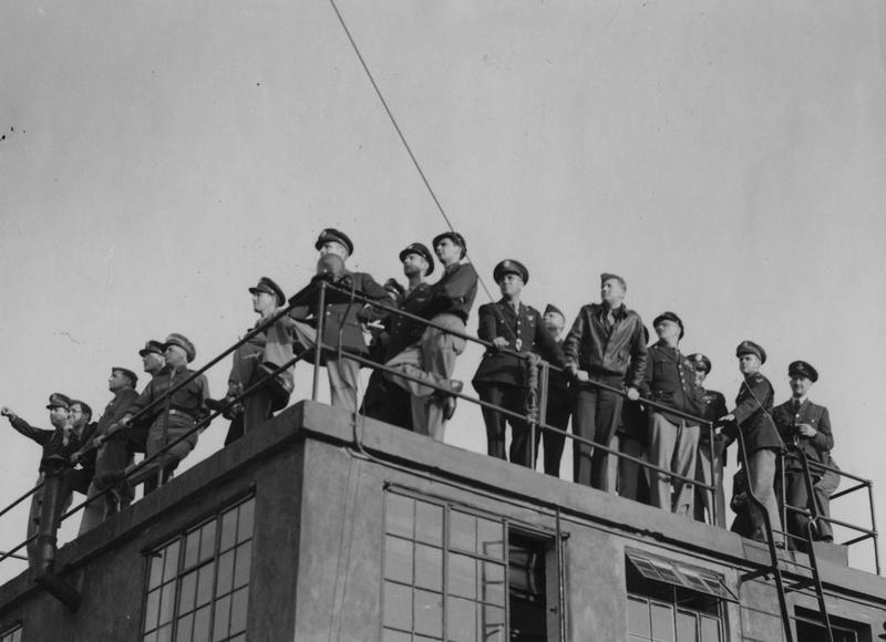 US and British Officers look out for the return of B-17 Flying Fortresses from the top of the Control Tower at Grafton Underwood after the 8th Air Force's first heavy bomber raid on 17 August 1942, over the Marshalling Yards at Rouen.   General Carl A Spaatz stands to the left of the ladder, Beirne Lay behind the guide rope and Fred Castle on the near corner. Many other officers from 8th Air Force Bomber Command are also present.   Image stamped on reverse: 'Photo Supplied Photopress Central.' [stamp], 'Passed for publication 18 Aug 1942.' [stamp], 'USA (BRI) CCC.' [written annotation] and '216036.' [Censor no.]   Printed caption on reverse: 'Picture shows: Aerodrome Personnel on the Control Tower watching for the return of the planes from the raid.' Handwritten caption on reverse: 'USAAF 1, 17/8/42 A.'