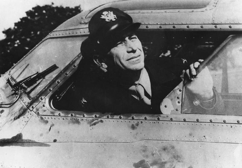 Colonel Frank A. Armstrong of the 97th Bomb Group in the cockpit of his B-17 Flying Fortress. Image stamped on reverse: 'Photographed by US Army Air Air Forces.' [caption], 'US Official Phot No. USB 230. (WA) Distributed by the Ministry of Information.' [caption] 'USAA(BRI)CCC:TYPE.' [written annotation] Printed caption on reverse: 'LEADER OF THE US BOMBING ATTACK ON WILHELMSHAVEN. Photo shows:- Col. Frank A. Armstrong of Asheville N.C. who led the bombing attack on Wilhelmshaven- the first American air attack on Germany in this war.'