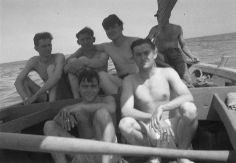 Personnel of the 100th Bomb Group, including John A Miller enjoy a boat trip in Italy. John A Miller, A veteran waist gunner of the 100th Bomb Group has handwritten on reverse: About June 30, 1944. We had left Russia + were based near Foggia, Italy. (1st shuttle raid to Russia- Italy) on this day we went up to Manfredonia + went swimming + sailing in the Adriatic Sea. Lt to Rt: Larry Townsend (P), Walt Kolar (TT), John A Miller (RW), Italian boatman. Front: Louis Glasser (R), Ed Fehrenkamp (CP). 5 of the crew of