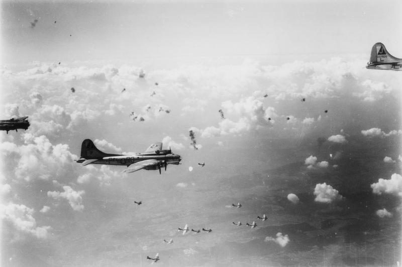B-17 Flying Fortresses of the 351st Bomb Group, including (RQ-P, serial number 42-97193) and (serial number 43-37920) fly through flak bursts during a mission. Handwritten caption on reverse: 'Thoison '557' took pic 20/7/44. Star Duster DS-L MIA 6/8/44.'