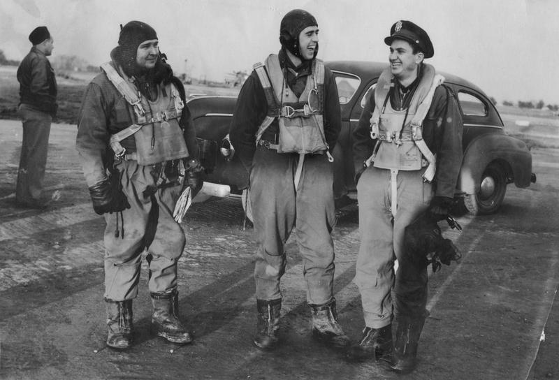 Colonel Lewis E. Lyle of the 379th Bomb Group shares a joke with his fellow airmen: Major Edwin H. Millson and Major James G. Edwards. A veteran has written beneath the image: 'Edwards, Millson, Lyle.' The same veteran has written on the reverse: 'Col Lew Lyle, 379BG Second Co jokes with Maj Ed Millson (centre) & Maj Jim Edwards (left) before a mission, late 1944. Lyle flew 69 missions between Nov 42 and Apr 45, a record surpassed by only one other 8AF pilot. Millson was Bombardier, Edwards Group Navigator.' A second veteran has handwritten on reverse: 'Jim Edwards Sq Navigator, Ed Millson Group Bombardier, Lew Lyle Group CO.'