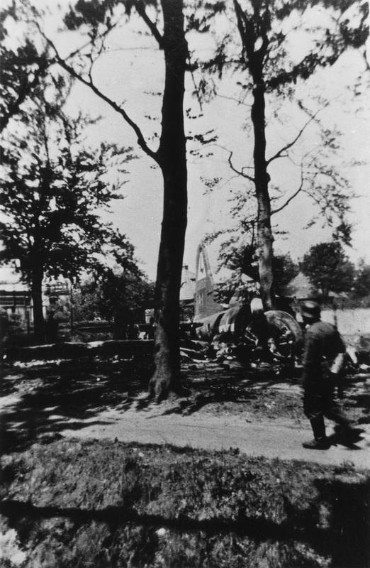 A Dutch soldier surveys the wreckage of a B-17 Flying Fortress of the 381st Bomb Group that has crashed near Apeldoorn. First Handwritten caption on reverse: '381BG, 30/7/43 by Fighters.' Second Handwritten caption on reverse: '42-3100, 381 BG, 532 BS. 3 KM SE of Apeldoorn, 30-7-43 10:45 Hrs. RNAF'