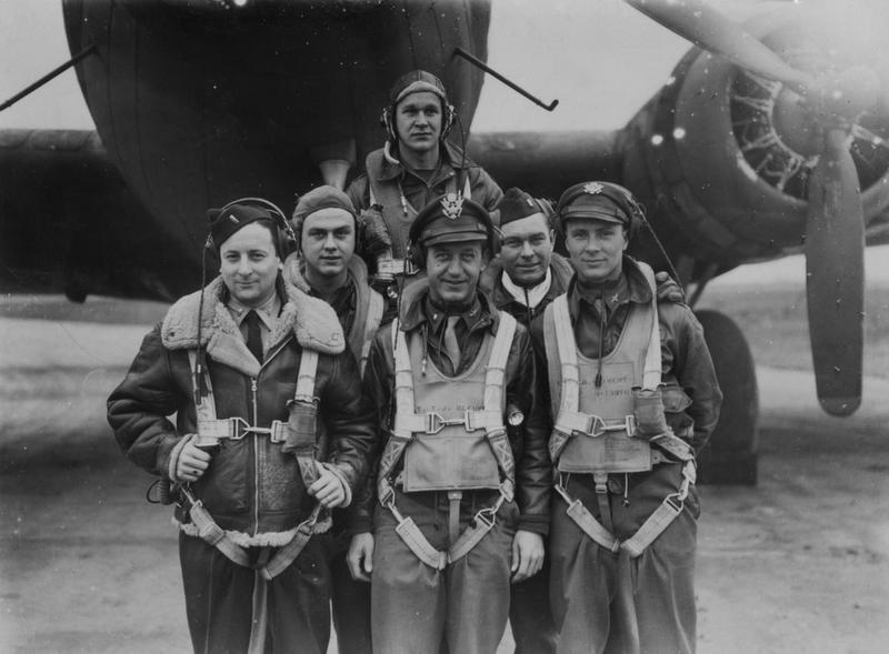 A bomber crew of the 385th Bomb Group with their B-17 Flying Fortress. Image stamped on reverse: 'Planet News.' [stamp], 'Passed for publication 6 Nov 1943.' [stamp] and '291701.' [Censor no.]   Printed caption on reverse: 'US AIRFORCE IN GREAT DAYLIGHT OFFENSIVE ON EUROPE. The great daylight offensive on Europe continues, targets in Germany, France and Belgium being attacked by great formations of bombers and fighters from the US Army Air Force and the RAF. Photo shows: Before they take off on the great Ruhr raid- six airmen who together represent 100 operations against the Nazis.   Left to right: front row  Lieut Fred D Albert, of Bronx NY navigator;  Lieut Theodore J Kleuser, of Little Rock Arkansas, co-pilot;  Lieut Ruel Weikert, of Dayton Ohio, pilot and commander of the aircraft.   Second row:  Tech. Sgt Darwin Mushrush, of Castaque, Pa; top turret gunner and engineer;  Lieut Tom Betow, of Marion, Wisconsin, bombardier.   Back row: Tech Sgt Walter Olowniuk of Detroit, Mich; radio gunner.   NC 6th November 1943. PN.'