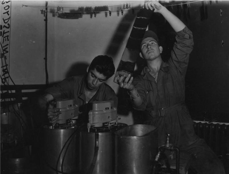 Staff Sergeant Francis Coughenour and Staff Sergeant Demetrio A Apadoca of the 385th Bomb Group develop intelligence photos from a mission. Image stamped on reverse; 'Keystone Press.' [stamp], 'Passed for Publication 15 Nov 1943.' [stamp] and '292890.' [Censor no.] Printed caption on reverse: 'FLYING FORTRESS PHOTOGRAPHERS. Without adequate photography, the fighting of this was by the Air Forces would be almost impossible. This is the story of how one Photo Unit on a Flying Fortress Station does its job of recording intelligence the bombing operations carried out by that station's heavy aircraft. The unit commanded by Lt Raymond Fordyce, of 3320, NW Fifth Ave, Miami, Florida, 26 year old former star athlete at Tampa University in Florida, includes aerial photographers who accompany the Forts on every mission and ground crewmen. US Pool/ SG/ Hel. Keystone. Photo shows: On their return, the film is rushed to the photo laboratory where it is immediately developed. Shown at work in the developing room are: S/Sgt Francis Coughenour, of Hutchinson, Kansas, and S/Sgt Demetrio A Apadoca, of Las Cruces, NM.'