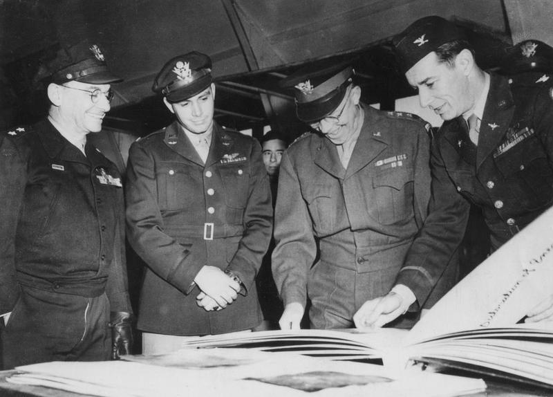 General Dwight D Eisenhower inspects photographs from a raid by the 386th Bomb Group. Image stamped on reverse: 'US Official Photo, Keystone Press.' [stamp], 21 Apr 1944.' [stamp] Printed caption on reverse :'US Official Photograph No. Distributes through OWI. Gen Eisenhower inspects raid photos. Nine Air Force Headquarters: During an inspection of a Ninth Air Force B-26 Marauder Medium Bombers station in England, General Dwight Eisenhower, Supreme Commander of the Allied forces in the European Theatre of Operations looks on strike photographs and is evidently tickled by them. With him are left to right: Major General Lewis H Brereton, commanding general of the Ninth Air Force, Lt Col Sherman E Beaty, the Chief and Col Herbert B Thatcher, commanding officer of a Ninth medium bomber base. 845/f. Keystone 479324.'