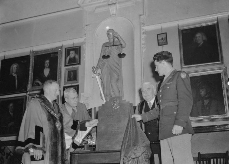 Lieutenant-Colonel Robert B Satterwhite of the 388th Bomb Group presents a plaque of behalf of the United States Eighth Air Force to the Mayor of Thetford, HR Watling, historian Professor Frank Dobie and Sir William Gentle to commemorate Thomas Paine. Image stamped on reverse: 'Associated Press.' [stamp], 'Passed for publication 25 Oct 1943.' [stamp] and '289762.' [Censor no.] Printed caption on reverse: Printed caption on reverse: 'AMERICAN SERVICEMEN'S TRIBUTE TO TOM PAINE. A Plaque in memory of Thomas Paine, one of the founders of American independence and author of