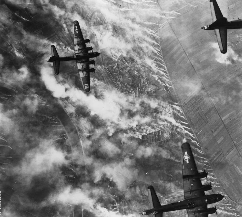 B-17 Flying Fortresses of the 388th Bomb Group fly over Nazi smoke screens. Printed caption on reverse: '73228 AC- The Nazis have released smoke screens in an effort to hide their railroad yards as Boeing B-17