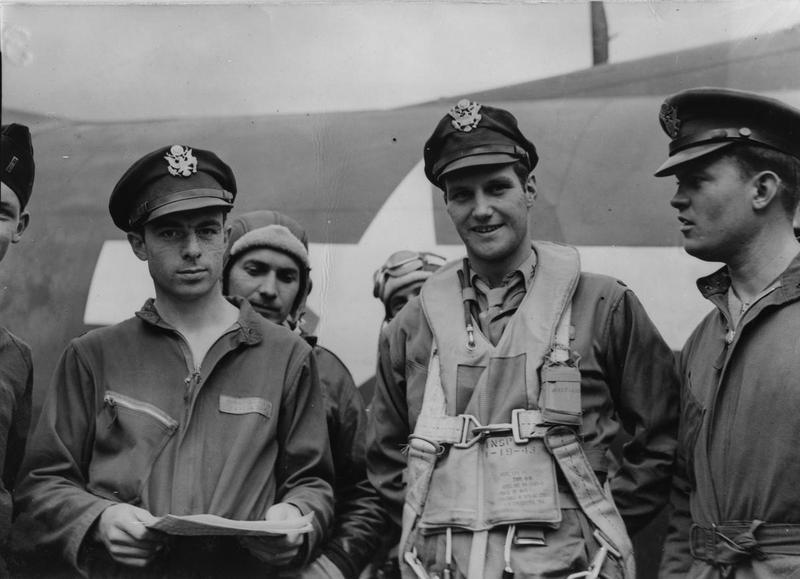Lieutenant John G Winant Jr of the 390th Bomb Group, wearing a Mae West life jacket, with his crew and B-17 Flying Fortress. Lieutenant Robert W Tredinnick, navigator, holds the papers.  Image stamped on reverse: 'Planet News.' [stamp], 'Passed for publication 15 Aug 1943.' [stamp] and '278783.' [Censor no.] Printed caption on reverse 'Photo shows: Lieut. John.G. Winant, Jnr. Leaving his Flying Fortress, at his station somewhere in England, after returning from a sortie over enemy territory G. Aug 1943 PN.'