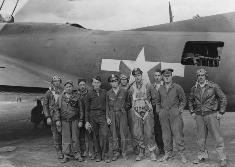 Lieutenant John G Winant Jr of the 390th Bomb Group, wearing a Mae West life jacket, with his crew and their B-17 Flying Fortress.   Image stamped on reverse: 'Planet News.' [stamp], 'Passed for publication 15 Aug 1943.' [stamp] and '278787.' [Censor no.]  Printed caption on reverse: ' Photo shows: Lieut. John G. Winant, Jnr. (centre, wearing a