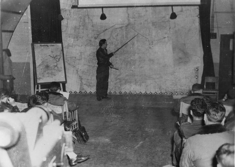 Personnel of the 390th Bomb Group are briefed by Major Louis W Dolan before the first shuttle mission to Russia. Image via Ian Mactaggart. Handwritten caption on reverse: '390 BG (2 photos) Maj Louise W. Dolan Ops officer briefs group for 1st shuttle to Russia Aircraft took off 21/6/44 MACTAGGART'