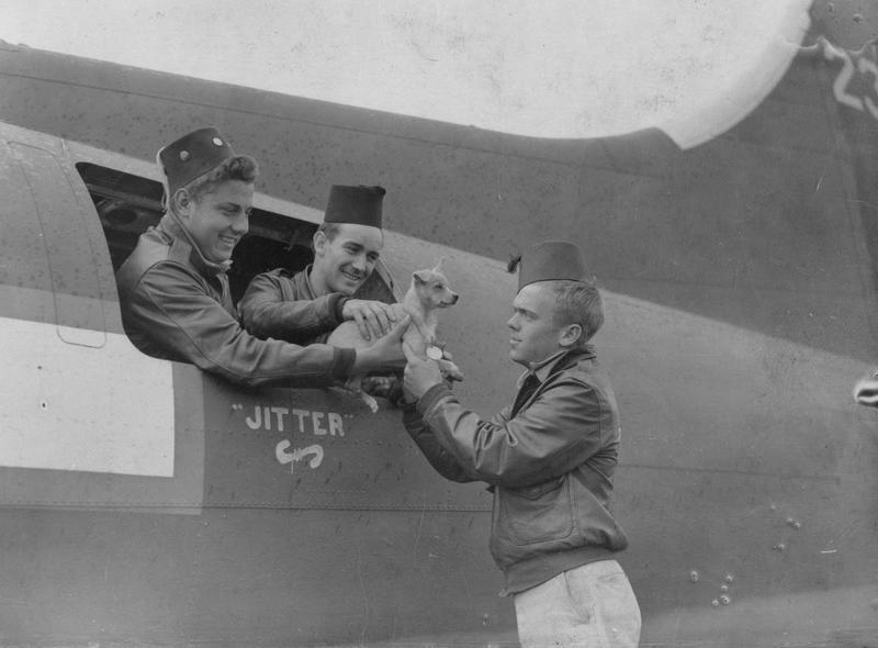 Sergeant Milton C Schwermer and Staff Sergeant Willis P Roy of the 390th Bomb Group pass their new dog mascot
