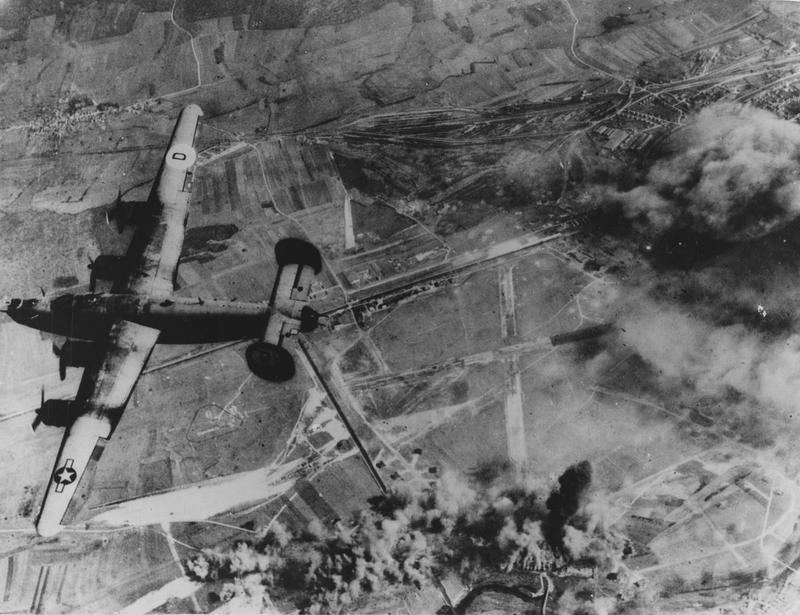 A B-24 Liberator of the 392nd Bomb Group successfully bombs an airfield near St Dizier, France. Image stamped on reverse: 'Keystone Press.' [stamp], '7 Jun 1944.' [stamp] Printed caption on reverse: 'NYP 21841 (KY). US PLANES BLAST GERMAN AIRFIELD IN FRANCE. A Liberator bomber of the Eighth US Army Air Force heads for its home base after helping to blast a German Airfield near St Dizier, in occupied France, where administrative building (upper right) burn fiercely and bombs explode on the dispersal area (lower centre). The airfield, located near the Marne River, is used by the Germans as a defensive fighter plane base. During March, 1944, American war planes flew 29,016 sorties over Germany and German-held Europe and hurled 30,176 tons of bombs on military and industrial targets.' Handwritten caption on reverse: '392BG successfully bombing German afield near St Dizier, France.'