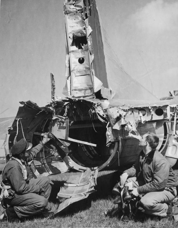 Two airmen of the 398th Bomb Group examine the damaged tail of a B-17 Flying Fortress. Damaged received while on the April 8,1945 mission to Derben, Germany. Just after bombs-away a direct hit by flak completely tore the tail gunner position away and disabled the rudder controls. The tail gunner, S/Sgt. Wallace E. Kasch, was carried away without his chute, his remains were never found. It took the skill of the two pilots, Lt. Col. Edwin B. Daily and 1st Lt. John L. Hahn, to get the aircraft back to base using the engines for directional control. MACR 13869