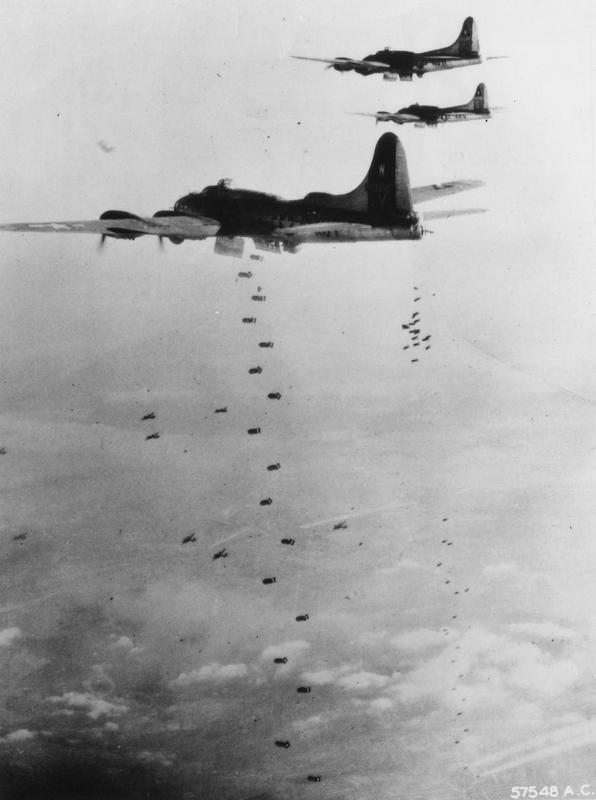 B-17s of the 398th Bomb Group bombing the railyard at Bingen, 29 December 1944. Printed caption on reverse: '57548 AC- With bomb bay doors open, the first of a large formation of Boeing B-17 Flying Fortresses send their bombs plummeting earthwards on rail installations at Bingen, Germany, as heavy bombers of US Eighth Air Force press home their attack of December 29, 1944. US Air Force Photo.'