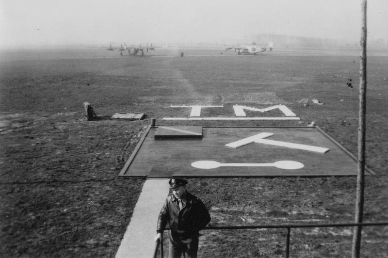 Signal Squares on the airfield at Tibenham, B-24 Liberators of the 398th Bomb Group are visible in the background. Handwritten caption on reverse: 'Tibenham Signal Squares.'