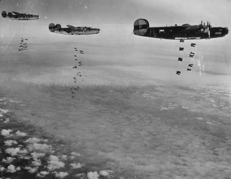 B-24 Liberators of the 446th Bomb Group drop bombs over their target. Image stamped on reverse: 'US Official Photograph.' [stamp], 'Sacred.' [stamp] Handwritten caption on reverse: 446 BG led by