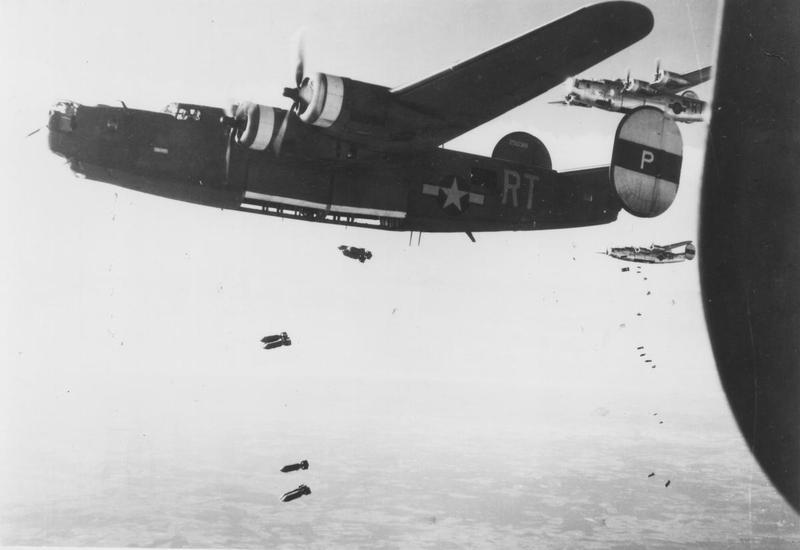 A B-24 Liberator (serial number 42-50318) of the 446th Bomb Group drops its load over the target area in Orleans, France during a mission with fellow Liberators. Printed caption on reverse: '81185 AC- Consolidated B-24's drop tons of bombs on the Nazi airdrome at Orleans, France during a raid on 14 June 1944.'