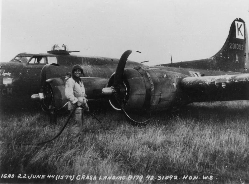 A ground crewman with a crashed B-17 Flying Fortress (serial number 42-31092) of the 447th Bomb Group. Official caption printed on image: 'ISAD 22 June 44 (1574) Crash Landing B17G 42-31092 HON WS.' Handwritten caption on reverse: 'Batch II.'