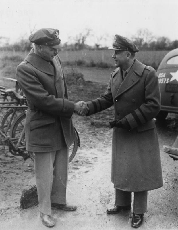 Colonel Thompson of the 448th Bomb Group (left) shakes hand with Brigadier General James P Hodges.   First handwritten caption on reverse: 'B/G James P Hodges (rt) with Col Thompson 448 BG (left).'  Second handwritten caption on reverse: '448 BG- 2nd BD Co General Hodges visiting Col Thompson.'