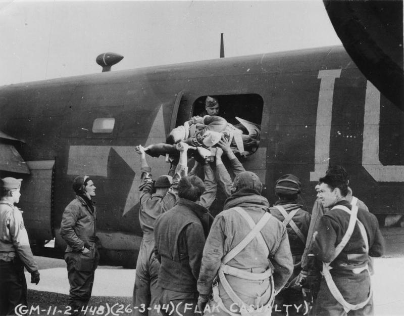 Airmen and ground crew of the 448th Bomb Group carefully transfer a flak casualty through the waist gun window of a B-17 Flying Fortress. Official caption printed on image: '(GM-11-2-448)(26-3-44)(Flak Casualty).' Handwritten caption on reverse: 'Col Patterson.'