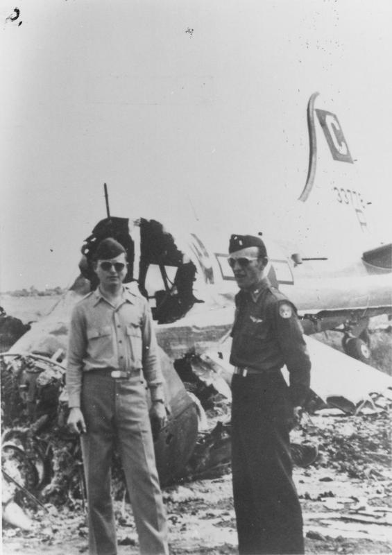"""Lieutenant Bill Gaither and Lieutenant John Stull of the 452nd Bomb Group with a B-17 Flying Fortress (serial number 43-37781) of the 96th Bomb Group that was destroyed by Luftwaffe bombers. Image via William C Gaither.   Letter from Gaither enclosed with print: 'These photographers were taken at Poltava, Russia on June 22 1944. On June 21st my group, the 452d and others flew from England to Poltava en route hitting oil refinery at Rhurland, Germany. That night after landing German dive bombers bombed the field destroying ninety or more B-17 aircraft. Our P-51 fighter escort which has landed at another field were denied permission to take off and intercept the German attack planes. My crew and I were assigned to the 730 Sq. My aircraft """"Borrowed Time"""". Was hit by an ME-109 over Yugoslavia. No 4 engine was knocked out and feathered, a hole was put in horizontal tail and hydraulic system damaged. Without brakes I ground looped on landing to stop the ship. There it remained isolated from the other ships which were destroyed that night. PHOTO NO 4- Lt Bill Gaither and Lt Stull and destroyed B-17. The Germans directed their attack at the B-17s and not at the crew's bivouac area. Only later did we learn that we were also a target- butterfly bombs were found in the tent area. Young Russians were used to search and destroy these bombs.'"""