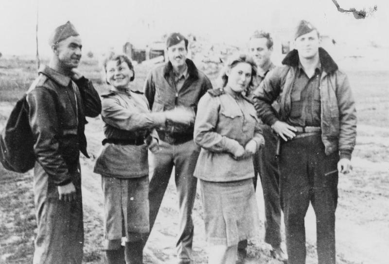 """Sergeant George Mondale, Lieutenant Ernest Demaray, Sergeant John McCallum and Lieutenant Roger Soth of the 452nd Bomb Group with Russian personnel. Image via William C Gaither. Letter from Gaither enclosed with print: 'These photographers were taken at Poltava, Russia on June 22 1944. On June 21st my group, the 452d and others flew from England to Poltava en route hitting oil refinery at Rhurland, Germany. That night after landing German dive bombers bombed the field destroying ninety or more B-17 aircraft. Our P-51 fighter escort which has landed at another field were denied permission to take off and intercept the German attack planes. My crew and I were assigned to the 730Sq. My aircraft """"Borrowed Time"""". Was hit by an ME-109 over Yugoslavia. No 4 engine was knocked out and feathered, a hole was put in horizontal tail and hydraulic system damaged. Without brakes I ground looped on landing to stop the ship. There it remained isolated from the other ships which were destroyed that night. PHOTO NO 8-"""