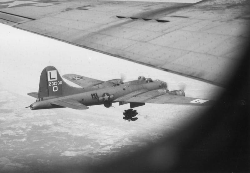 A B-17 Flying Fortress (serial number 42-31330) of the 452nd Bomb Group releases its bombs over an airdrome in Bordeaux. Printed caption on reverese: '61732 AC- BOMBS AWAY!!!! A Beoing B-17
