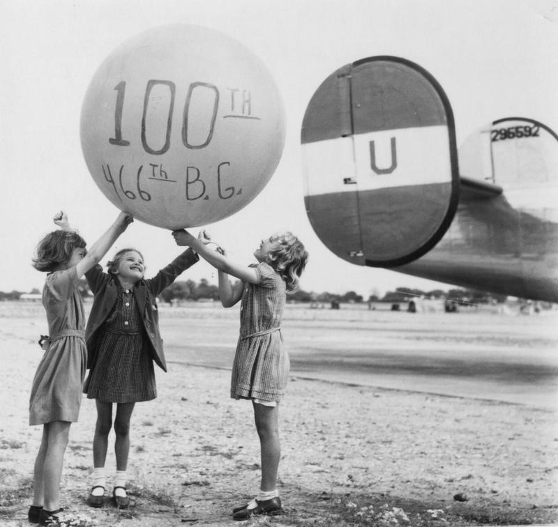 Three little girls hold up a balloon celebrating the 100th mission of the 466th Bomb Group in front of a B-24 Liberator (serial number 42-95592) nicknamed