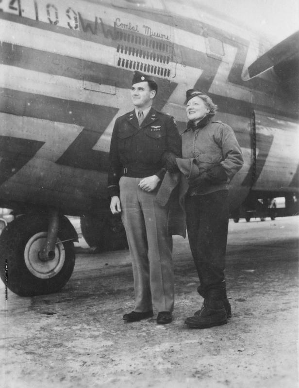 An airman of the 466th Bomb Group and an airwoman of the Women's Army Corps, with a B-24 Liberator used as a flight assembly ship. 41-24109WW