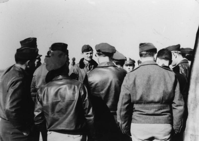 Personnel of the 491st Bomb Group at a mission briefing. Handwritten caption on reverse: 'Final Briefing Rhine Supply Mission 3-24-45. Capt Miskewich facing in cap, think in the jacket in foreground- Reed.'