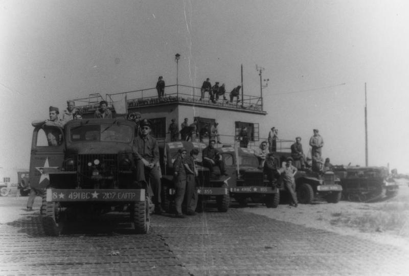 Personnel of the 491st Bomb Group with ground support vehicles, including trucks, ambulances and a Cletrac wait in front of the control tower at Metfield for returning B-24 Liberators. Handwritten caption on reverse: 'Waiting for mission return, probably Metfield, Nov.'