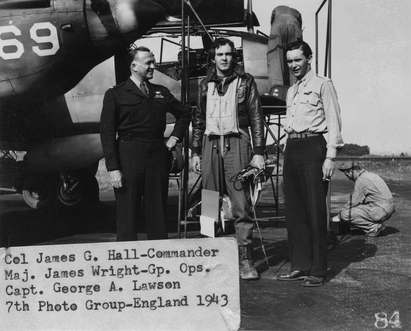 Colonel James G Hall, Commander, Major James Wright, Group operations and Captain George A Lawson of the 7th Photographic Reconnaissance Group with the nose of an F-5 Lightning. 1943. Image stamped on reverse: 'Passed by AAF STA 234. Not to be published.' [stamp]