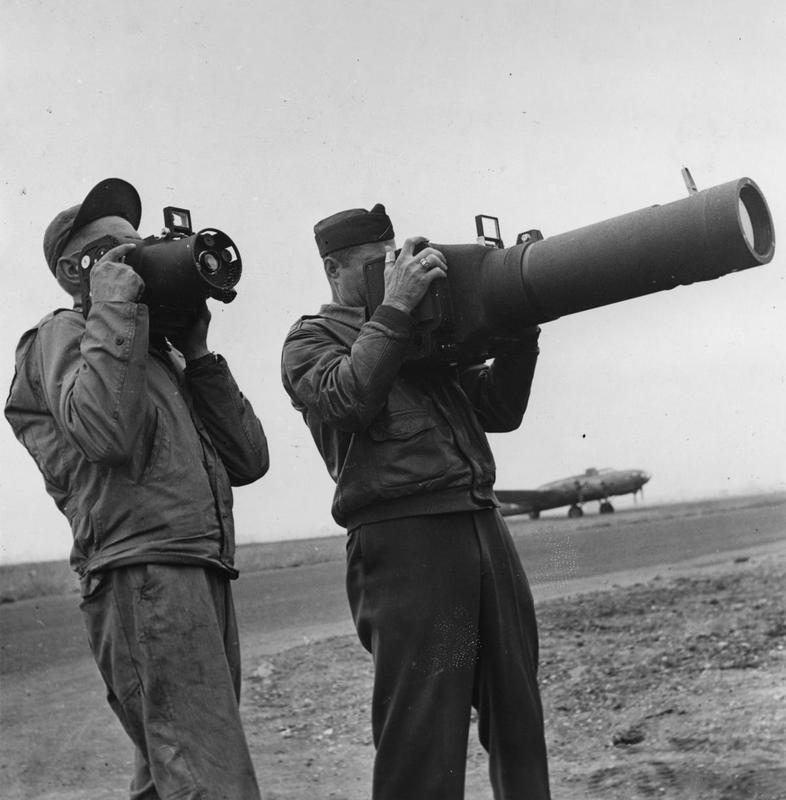 Photographic officers of the 7th Photographic Reconnaissance Group look through camera lenses infront of a B-17 Flying Fortress. Image stamped on reverse: 'Esten Illustrated.' [stamp], 'Passed for Publication 8 Jul 1943.' [stamp] and '273528.' [Censor no.]. A printed caption was previously attached to the reverse, however this has been removed.