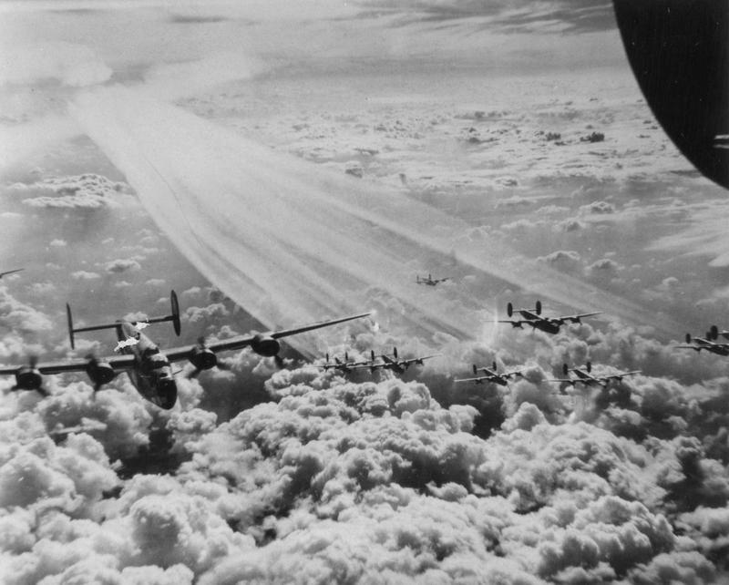 A flight of B-24 Liberators of the 446th Bomb Group fly in formation above the clouds.