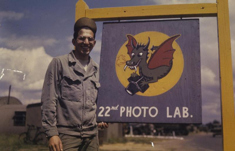 Staff Sergeant Robert Astrella of the 7th Photographic Reconnaissance Group with the signboard of the 22nd Photographic Laboratory at Mount Farm. Image by Robert Astrella, 7th Photographic Reconnaissance Group. Written on slide casing: 'Mount Farm.'