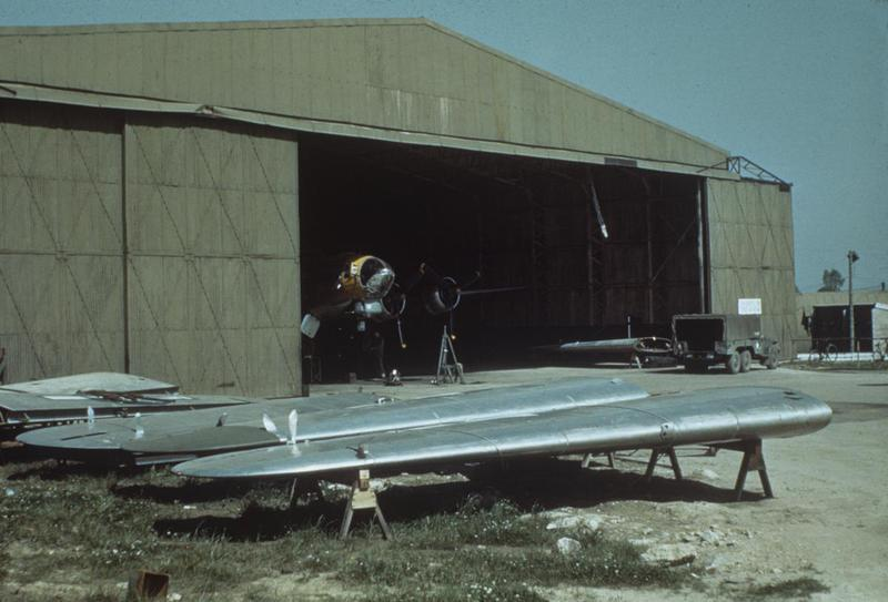 A B-17 Flying Fortress of the 34th Bomb Group inside a hangar. Image via Mark Brown, AFA. Written on slide casing: 'B-17 Yellow Hangar.' Note: This slide is shown reversed. The truck should be facing the left of the picture. Update 23/08/15. Location is Mendlesham at the south entrance to the western T2 hangar. The hangar still exists as part of an industrial complex. The aircraft is the 'Missbehaven Raven' tail code 43-38280 . Close analysis of the nose shows a white swastika above the cheek gun. The 'Valour to Victory' website lists the aircraft's ball turret gunner as being credited with a kill on 2nd March 1945. Additional bomb tallies plus daisies in the grass suggest this photograph is April 1945.  Wing sections in the foreground plus inside the hangar entrance (note fuel cell) suggest multiple aircraft structure repairs are happening here. Note the support jack near the propeller. Aircraft was involved in a propwash incident on 5th April 1945. The aircraft didn't fly again until 10th April 1945 which was quite a break in missions. It's a reasonable assumption to say this photograph was taken in that 5 day period, especially as no further damage reported after this time period thus little need for entry into a hangar. The incident on 5th April resulted in 3 crew bailing out at 20,000ft. 2nd Lieutenant Leo T Bartczak was killed probably attempting to bail out. He is buried in Madingley American Cemetery.