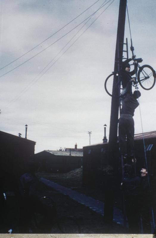 Personnel of the 44th Bomb Group hoist a bicycle up a telegraph pole at Cheddington (Marsworth). Image via R Seaver.