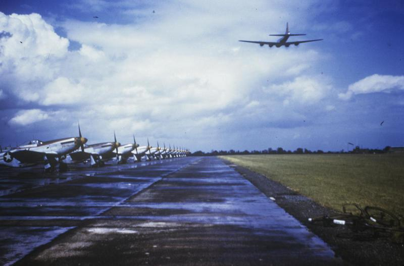 A B-17 Flying Fortress overflying an airfield runway, upon which are parked a line of P-51 Mustang aircraft, of the 343rd Fighter Squadron, 55th Fighter Group. Handwritten on slide: