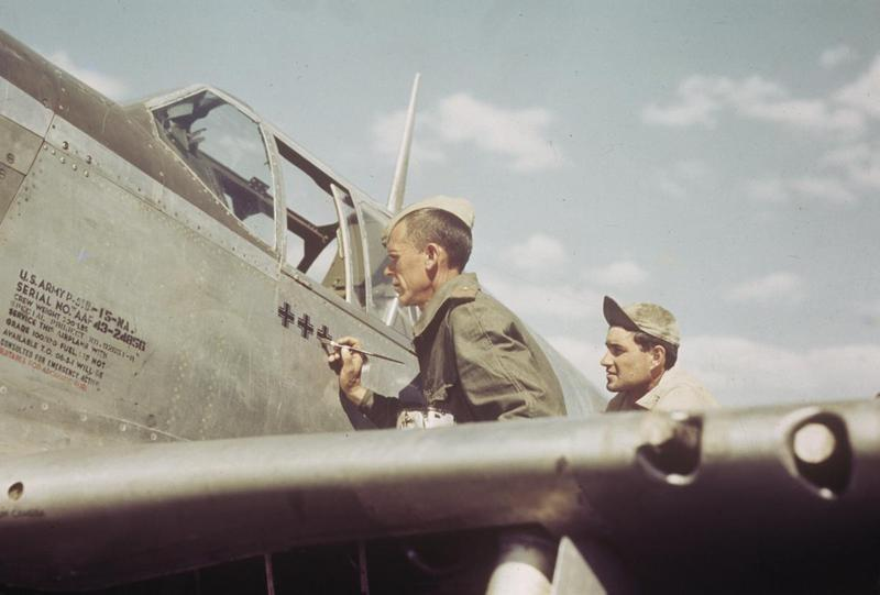 An airman of the 325th Fighter Group, 15th Air Force paints a