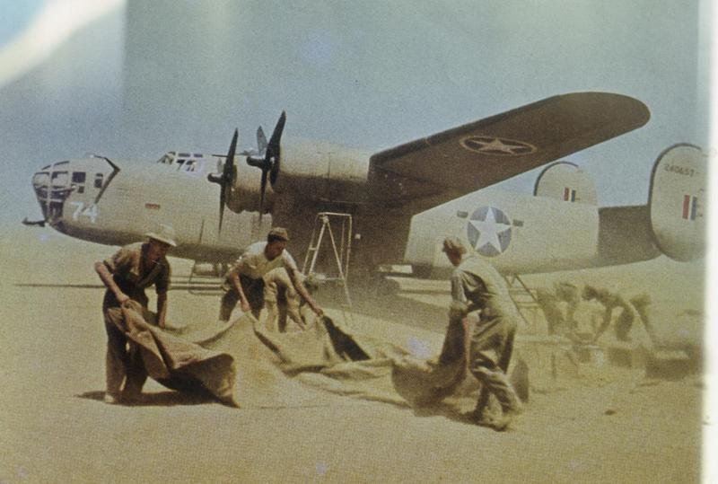 Personnel of the 376th Bomb Group lift dust sheets to protect their equipment infront of a B-24 Liberator (serial number 42-40657) nicknamed