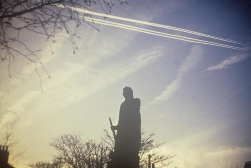 Fighter aircraft leave contrails above the Lord Nelson monument in Norwich. Photographed by an airman of the 458th Bomb Group. Image via RM Eselgroth. Written on slide casing: 'Fighter contrails over Norwich, 1/45. Nelson monument.'
