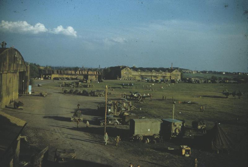 Personnel of the 10th Photographic Reconnaissance Group at Fürth airfield in Germany. F-5 Lightnings and a captured FW 190D are visible in the background. Image via R Woolner. Written on slide casing: 'Fürth 5/45, 10 PG.'