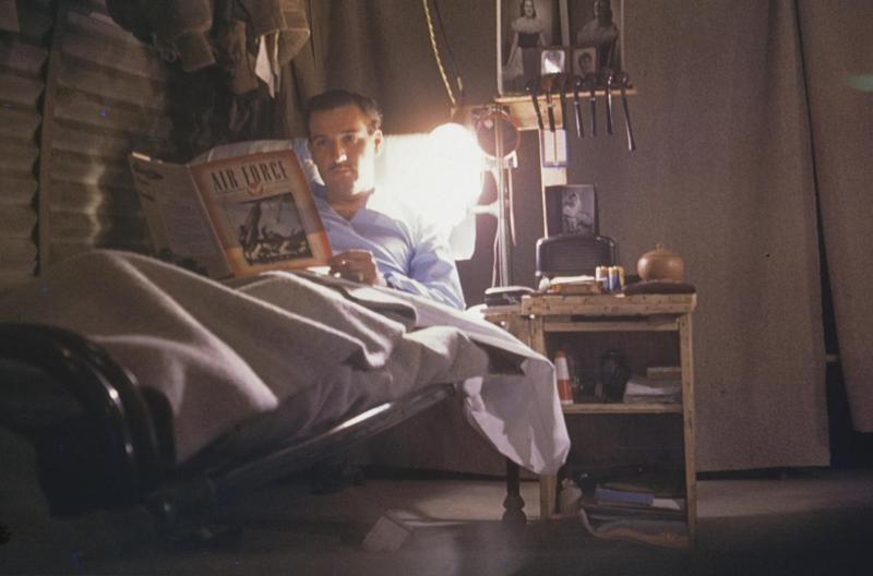 Lieutenant Jack Havener of the 344th Bomb Group reads a magazine in his bunk. Image by Jack K Havener, 344th Bomb Group.. Associated caption: 'Havener in his sack in the hut. Night stand and racks & shelving made from empty ammo boxes, Sept `1944.'