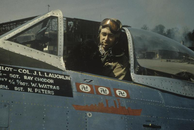 Colonel J.L. Laughlin, of the 362nd Fighter Group, smokes a cigar with his dog mascot