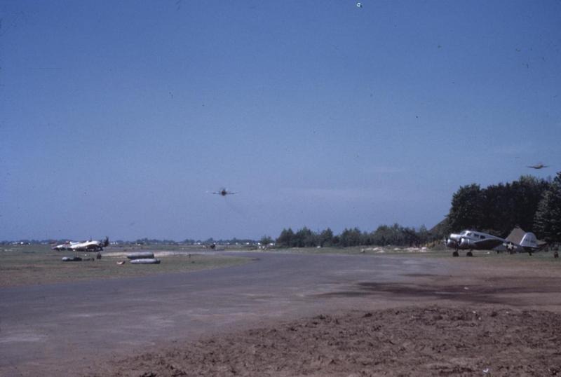A P-47 Thunderbolt of the 406th Fighter Group flies low over fellow P-47s.